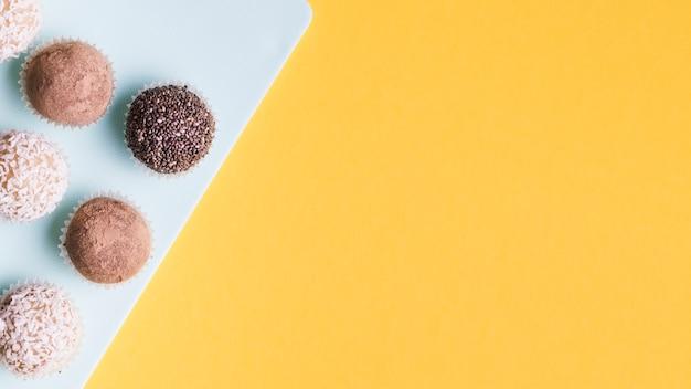 Una varietà di palline di cioccolato sul bordo bianco contro sfondo giallo