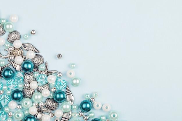 Una varietà di perle per fare collane. sfondo blu tema nautico