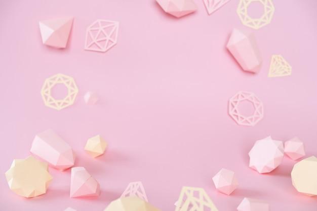 Una varietà di pietre preziose sfaccettate, fatte di carta su uno sfondo rosa.