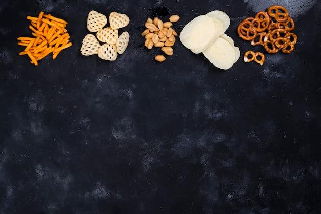 Una varietà di snack e snack per la birra su un tavolo nero di cemento