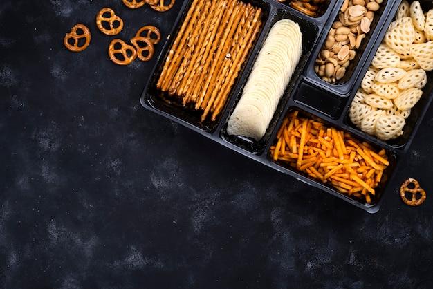 Una varietà di snack sulla scatola per la birra su un tavolo nero di cemento