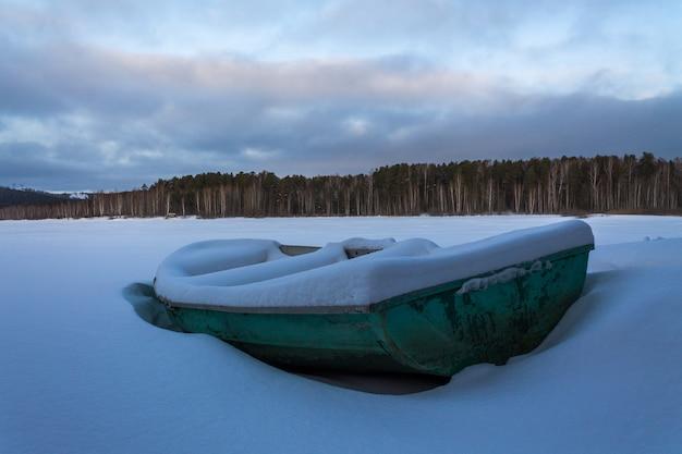 Una vecchia barca verde in un lago ghiacciato. barca coperta di neve pura