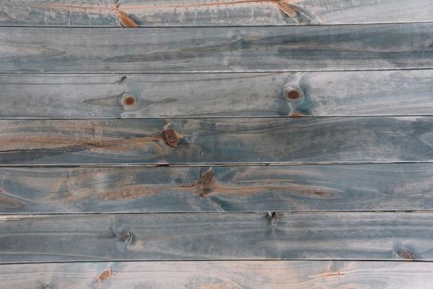 Una vecchia plancia di legno martellata colorata grigia