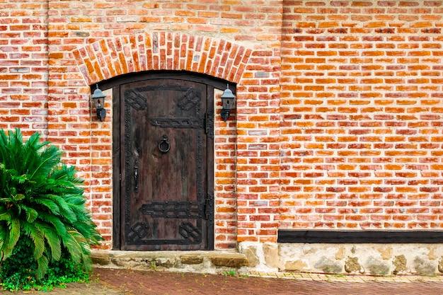 Una vecchia porta di legno massiccia chiusa con tende da sole in ghisa e bussare alla maniglia della porta a forma di anello contorto, lanterne vintage appese su entrambi i lati su un muro di mattoni rossi.