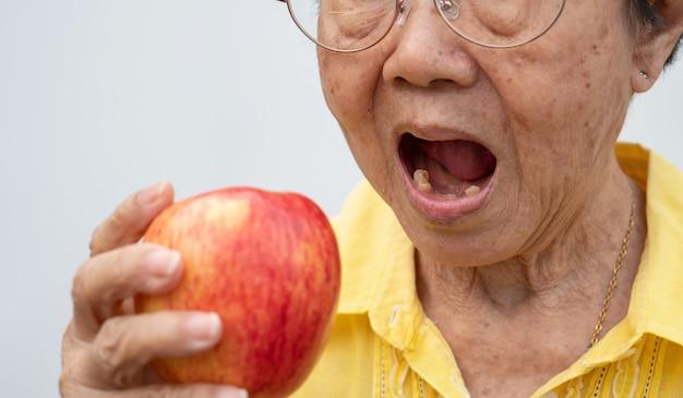 Una vecchia porta gli occhiali e senza denti cerca di mangiare mele rosse.