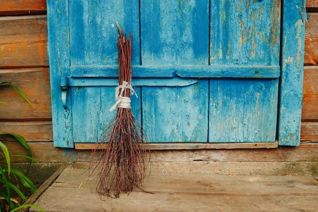 Una vecchia scopa sulla porta di legno