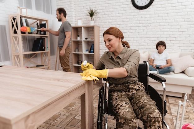 Una veterana su una sedia a rotelle sta pulendo la casa.
