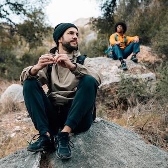 Una viandante di due maschi che si siede sulla roccia