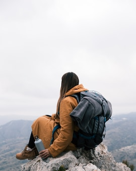 Una viandante femminile che si siede sul picco della montagna che tiene bottiglia disponibila che guarda