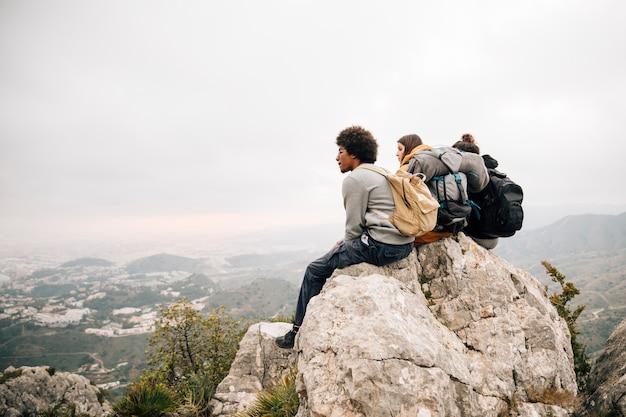 Una viandante maschio che si siede sul picco di montagna che esamina vista
