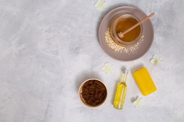Una visione elevata del miele; sapone giallo; bottiglia di olio essenziale; polvere di caffè con fiori bianchi su sfondo concreto