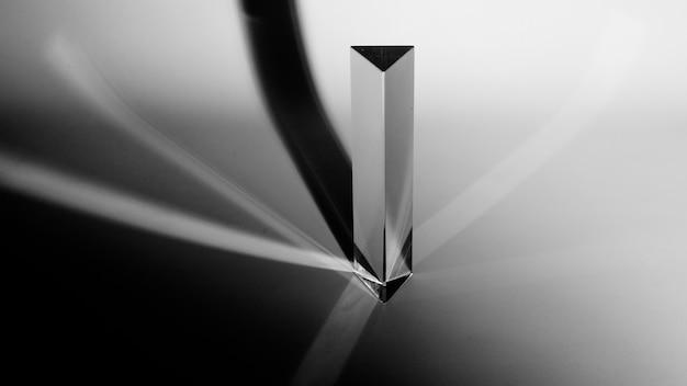 Una visione elevata del prisma triangolo con ombra scura su sfondo grigio