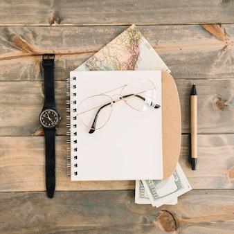 Una vista aerea degli occhiali sul blocco note a spirale; moneta; carta geografica; orologio da polso e penna su fondo in legno della plancia