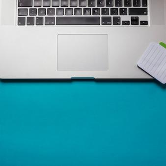Una vista aerea del blocco note sul portatile su sfondo blu