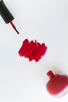Una vista aerea del colpo dello smalto per unghie e della bottiglia su fondo bianco