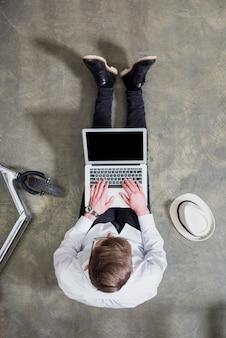 Una vista aerea del giovane che si siede sul pavimento di calcestruzzo facendo uso del computer portatile