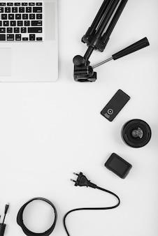Una vista aerea dell'accessorio della fotocamera con il computer portatile su priorità bassa bianca