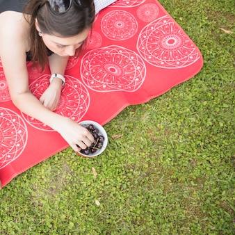 Una vista aerea della donna che si trova sulla coperta che mangia ciliegia