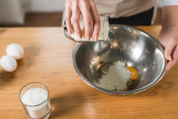 Una vista aerea della donna versando la farina nell'utensile sul tavolo di legno