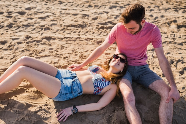 Una vista aerea della giovane donna alla moda che si trova sul giro del suo amico del ragazzo che si siede sulla sabbia alla spiaggia