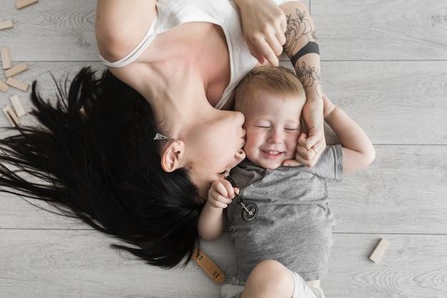 Una vista aerea della giovane donna sdraiata sul pavimento in legno baciare suo figlio
