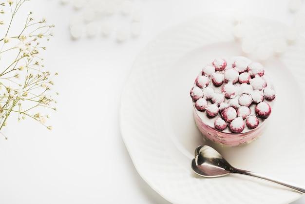 Una vista aerea della torta deliziosa con il cucchiaio di forma del cuore sul piatto bianco contro il contesto bianco