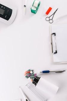 Una vista aerea delle attrezzature mediche con la lavagna per appunti su fondo bianco