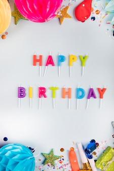 Una vista aerea delle candele variopinte di buon compleanno con gli elementi del partito sul contesto bianco
