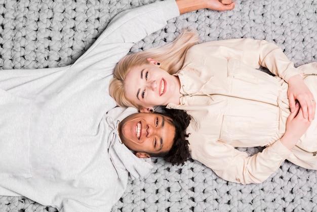 Una vista aerea delle giovani coppie interrazziali sorridenti che si trovano sulla coperta grigia