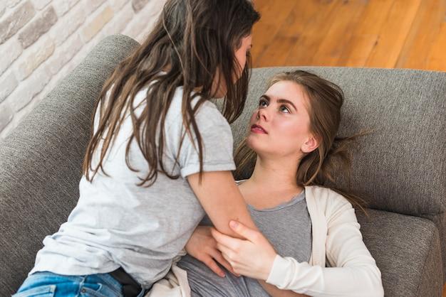Una vista aerea delle giovani coppie lesbiche che si trovano sul letto grigio