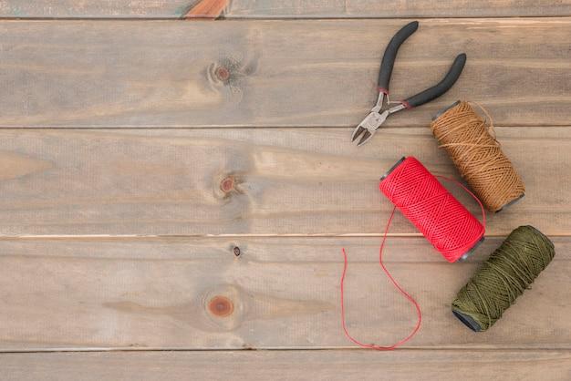 Una vista aerea delle pinze e bobine colorate del filato sullo scrittorio di legno