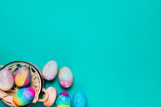 Una vista aerea delle uova di pasqua dipinte ad acquerello su sfondo turchese