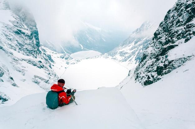 Una vista aerea dello sciatore che si siede sulla cima della montagna nevosa delle alpi