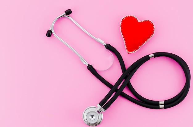 Una vista aerea dello stetoscopio con cuore tessile rosso su sfondo rosa