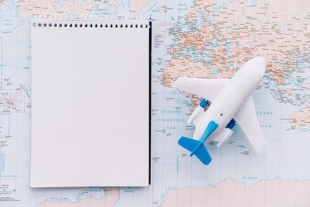 Una vista aerea di aeroplano bianco giocattolo e blocco note vuoto spirale sulla mappa