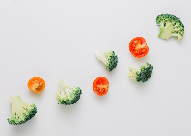 Una vista aerea di broccoli incrociati e pomodorini dimezzati su sfondo bianco