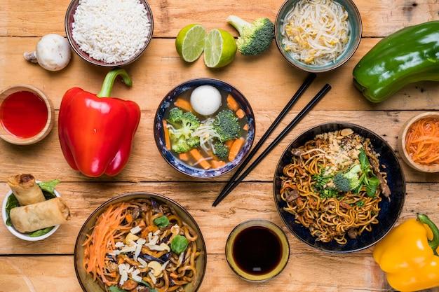 Una vista aerea di cibo tailandese tradizionale con salse sulla tavola di legno