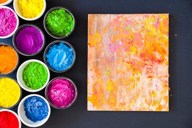 Una vista aerea di colore in polvere vicino a tavola di legno su sfondo nero
