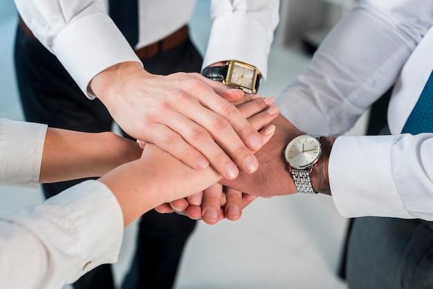 Una vista aerea di imprenditore e imprenditrice accatastamento mani