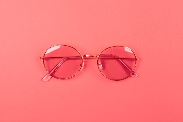 Una vista aerea di occhiali da sole su sfondo corallo