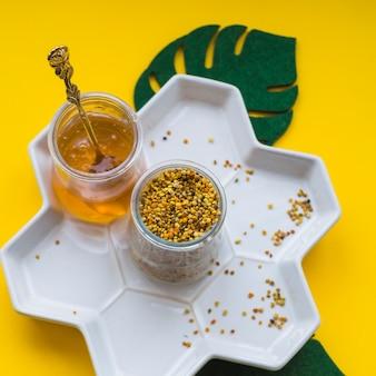 Una vista aerea di polline d'api e miele nel vassoio bianco su sfondo giallo