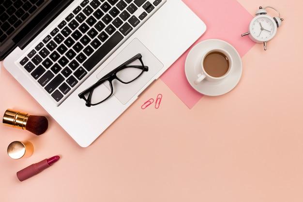 Una vista aerea di prodotti cosmetici trucco, occhiali da vista, computer portatile, tazza di caffè e sveglia sullo sfondo pesca