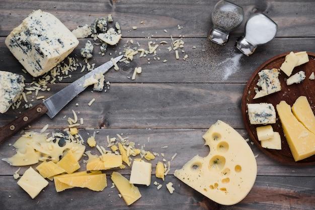 Una vista aerea di sale e pepe shaker con formaggio sulla scrivania in legno