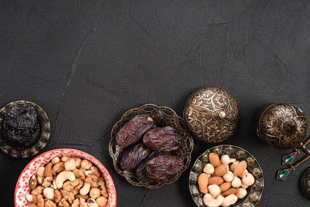 Una vista aerea di succosi e deliziosi datteri e noci in ciotola metallica su sfondo concreto