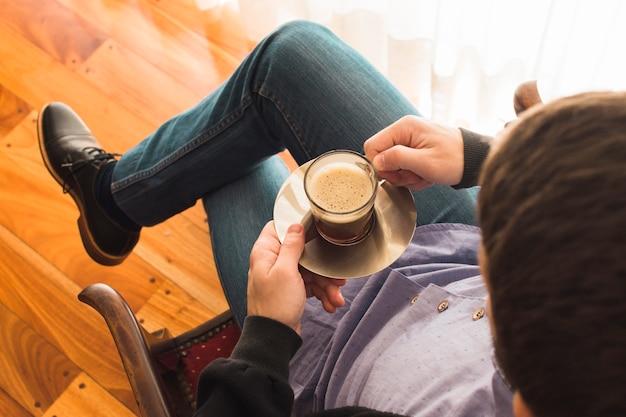 Una vista aerea di un uomo che si siede sulla sedia del bracciolo che tiene tazza di caffè
