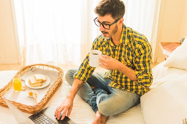 Una vista aerea di un uomo seduto sul letto tenendo la tazza di caffè con laptop