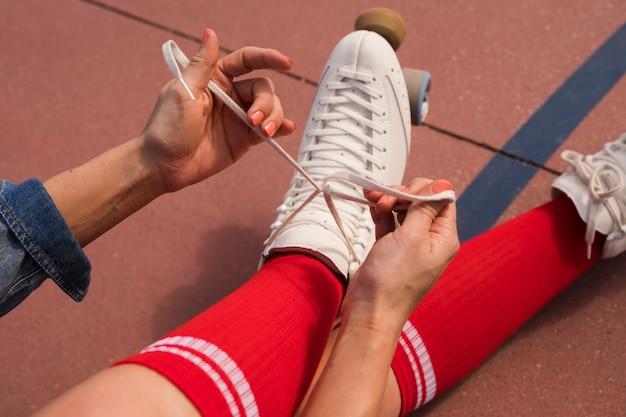 Una vista aerea di una donna seduta sul terreno che lega il merletto del pattino a rotelle