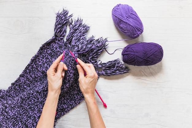 Una vista aerea di una persona che lavora a maglia sciarpa viola sul contesto strutturato bianco