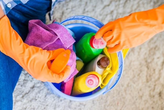 Una vista aerea di una persona che prende bottiglia spray dal secchio blu