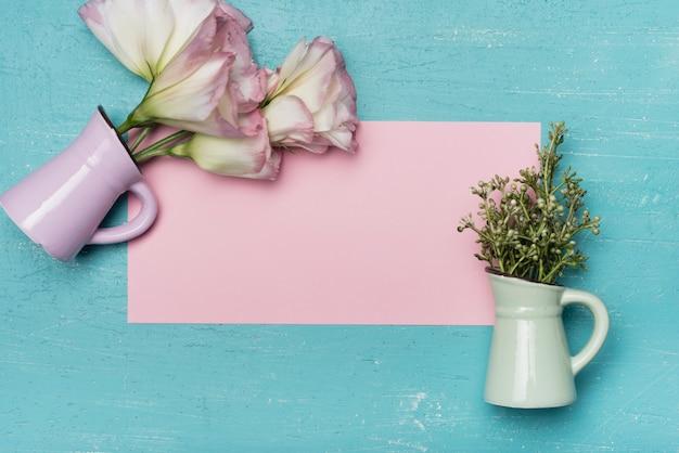 Una vista aerea di vasi in ceramica su carta bianca rosa su sfondo blu in legno